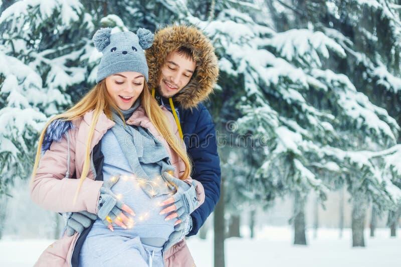 Zwanger paar in de winter stock afbeeldingen
