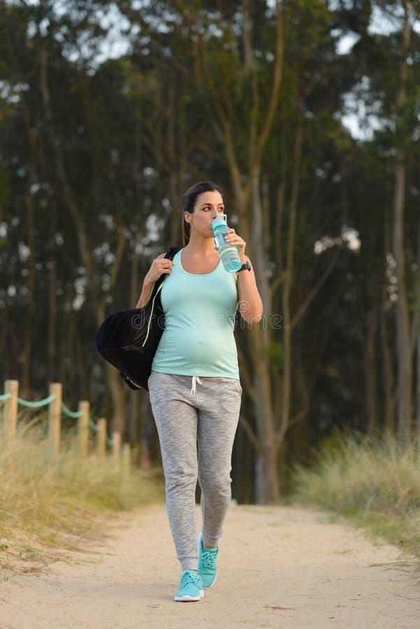 Zwanger sportief vrouwen drinkwater na openluchttraining royalty-vrije stock foto's