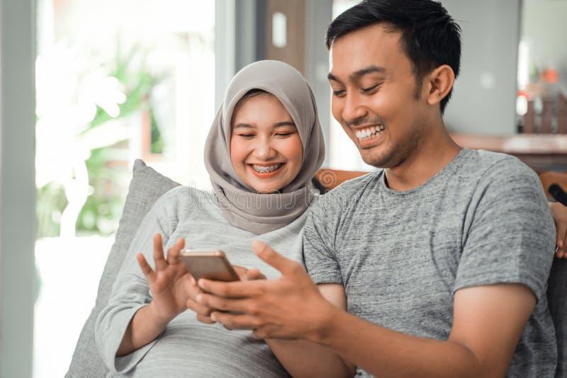 Zwanger vrouw en echtgenoot die smartphone gebruiken royalty-vrije stock foto