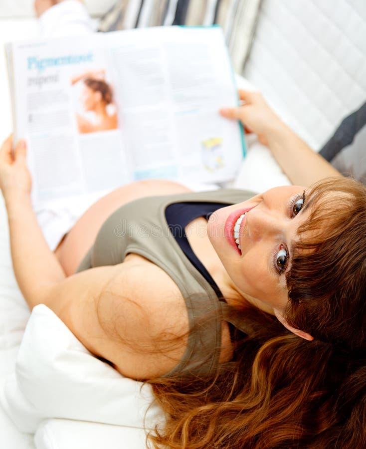 Zwanger vrouwelijk lezingstijdschrift op bank thuis stock foto's