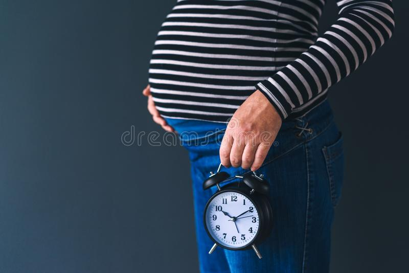Zwanger wijfje met uitstekende wekker royalty-vrije stock fotografie