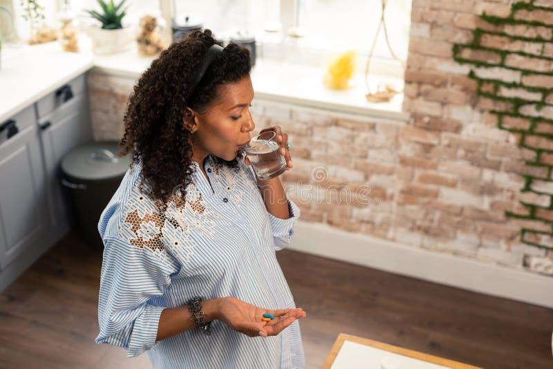 Zwangere dame die haar vitaminen met water nemen stock afbeeldingen