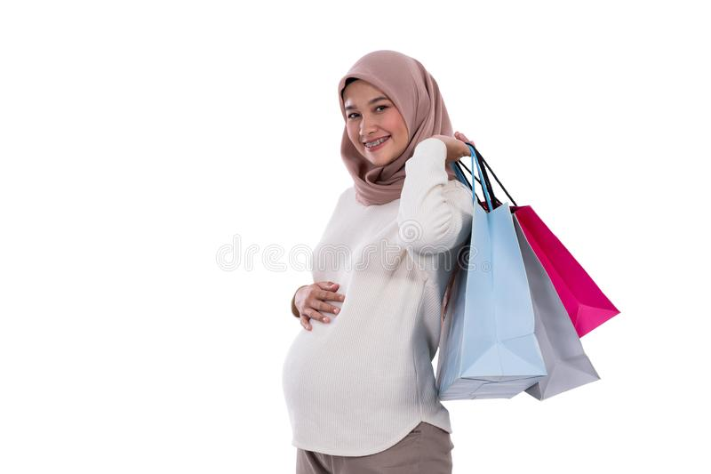 Zwangere de vrouw toont veel het winkelen zakken stock foto