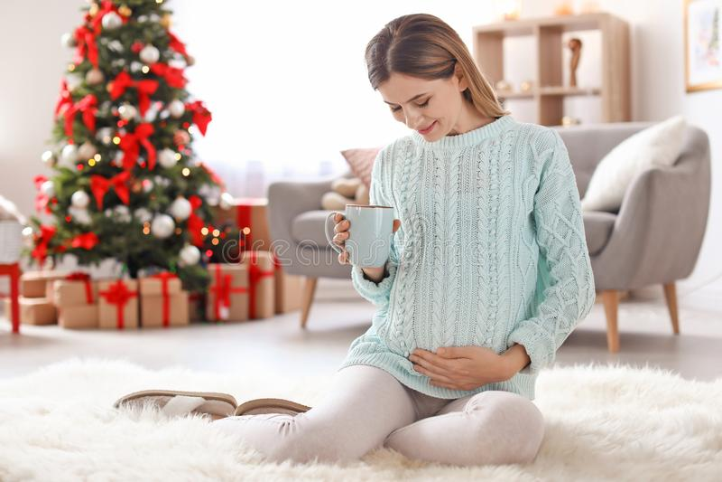 Zwangere die vrouw met kop theezitting op vloer in ruimte voor Kerstmis wordt verfraaid stock foto's
