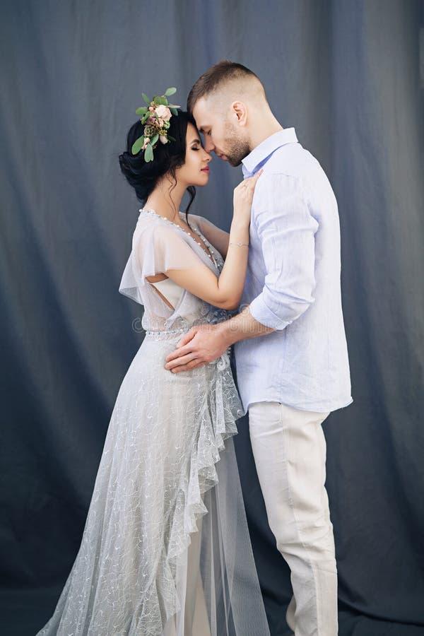 Zwangere Europese vrouw met haar echtgenoot op grijze achtergrond, jong Europees paar die op een kind, prenant vrouw wachten royalty-vrije stock afbeeldingen