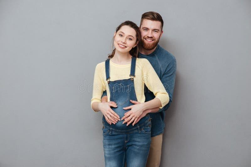Zwangere gelukkige vrouw die de vrolijke mens koesteren stock foto's