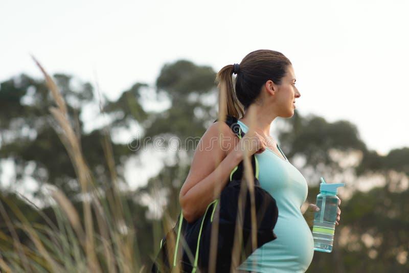 Zwangere gemotiveerde vrouw op openluchtgeschiktheids gezonde training stock foto