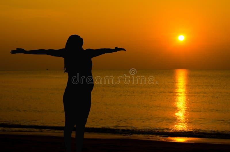 Zwangere het doen yoga op het strand stock fotografie