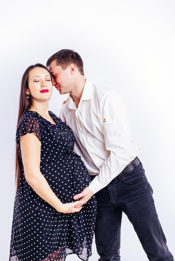 Zwangere jonge vrouw die op haar kind met een echtgenoot wachten stock fotografie