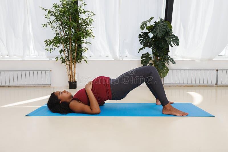 Zwangere jonge vrouw die op yogamat uitoefenen royalty-vrije stock foto