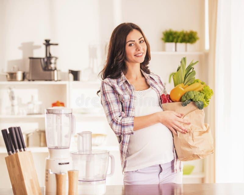 Zwangere Jonge Vrouw in Keuken met Pakket royalty-vrije stock afbeelding