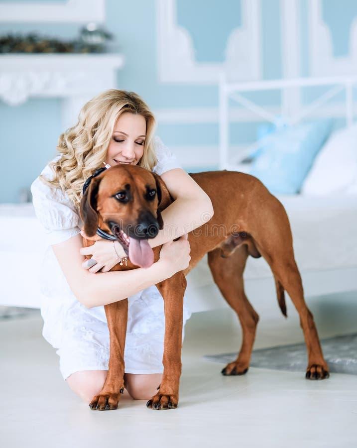 Zwangere jonge vrouw met haar huisdierenzitting op bed in slaapkamer royalty-vrije stock fotografie