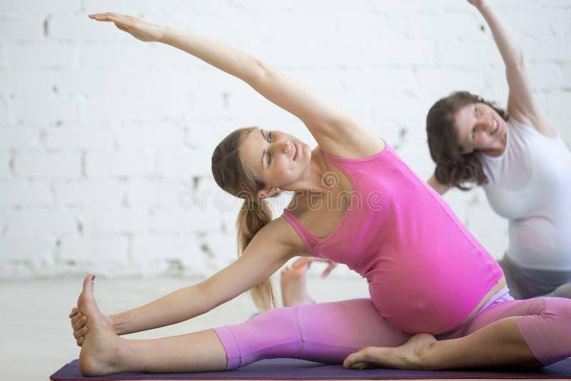 Zwangere jonge vrouwen die prenatale yoga doen Het buigen in Janu Sirsas stock foto's