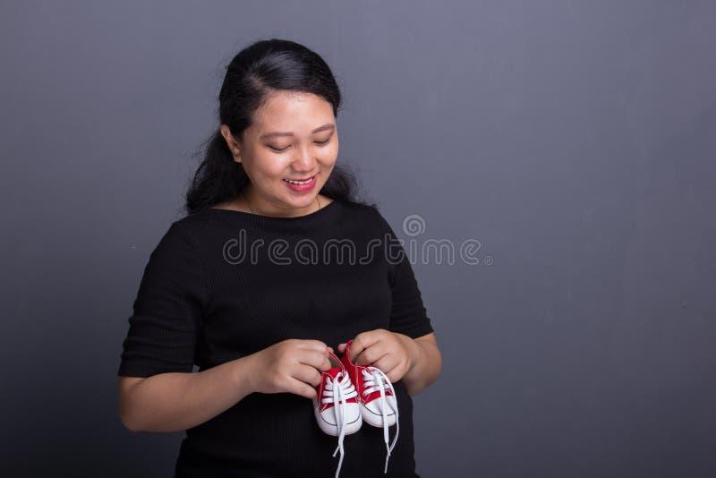 Zwangere mama die een paar kleine rode tennisschoenen houden royalty-vrije stock afbeeldingen