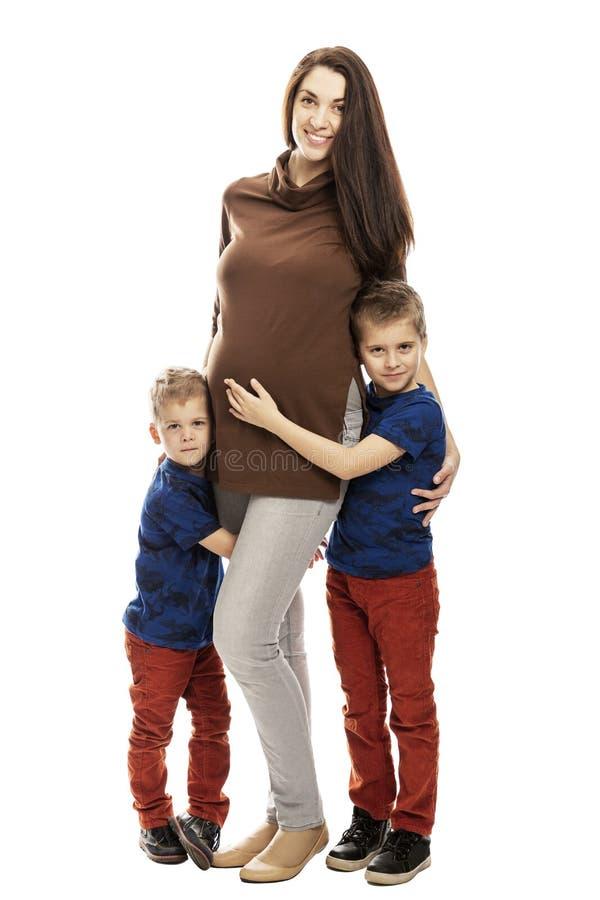 Zwangere mamma en zonenomhelzing en glimlach, volledige hoogte Tederheid en liefde Ge?soleerdj op witte achtergrond stock fotografie