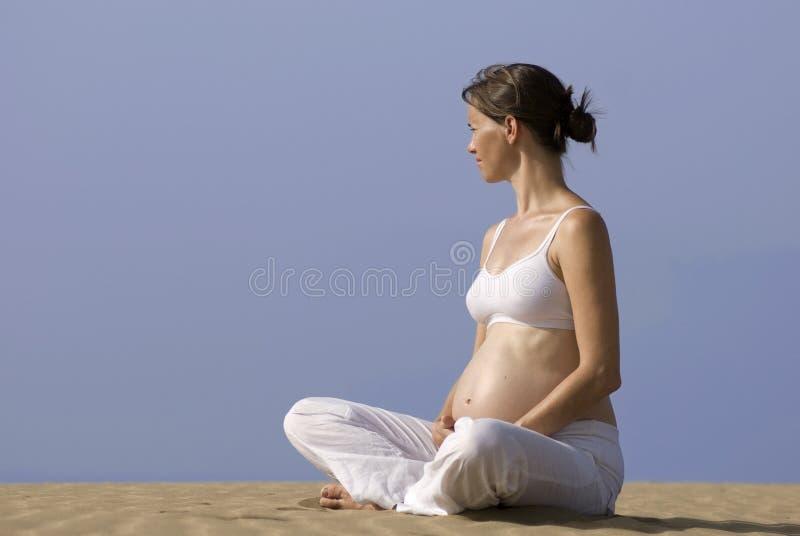 Zwangere meisjeszitting op het zand stock foto's