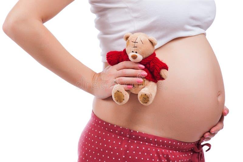 Zwangere moeder die haar buik tonen en teddy houden stock foto's