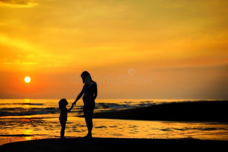 Zwangere moeder en een kind door het overzees stock foto