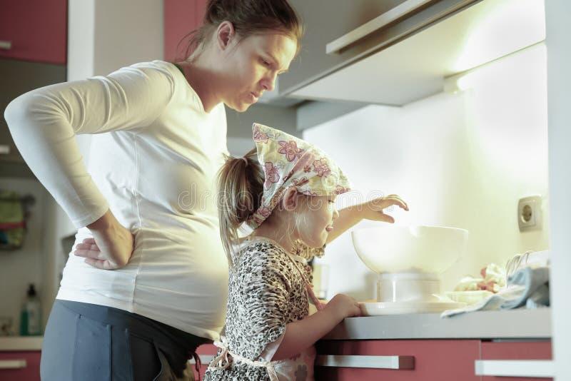Zwangere moeder en haar dochter het koken in de keuken stock foto's