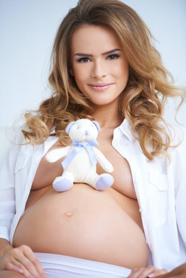 Zwangere moeder met een schitterende glimlach stock afbeeldingen
