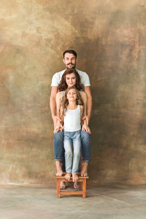 Zwangere moeder met tienerdochter en echtgenoot Het portret van de familiestudio over bruine achtergrond stock foto