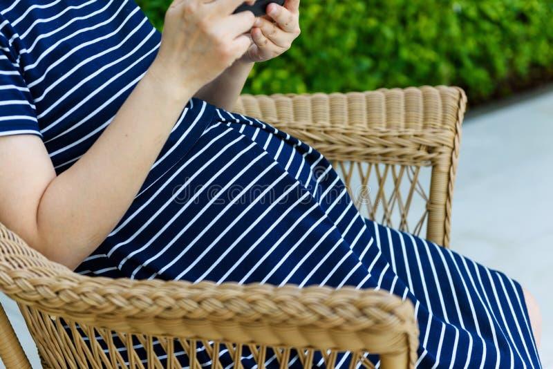 Zwangere smartphone van het vrouwenspel terwijl het zitten royalty-vrije stock foto's