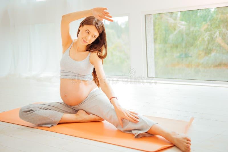 Zwangere sportieve vrouw die en gymnastiek- oefeningen zitten maken royalty-vrije stock foto