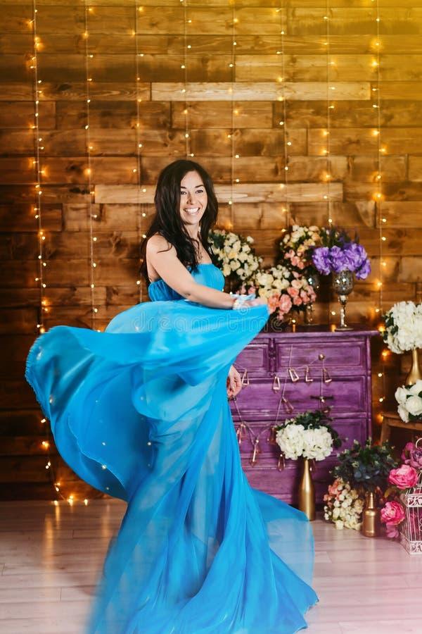 Zwangere vrolijke mooie die vrouwentribunes in zijdestof en lach worden verpakt royalty-vrije stock foto
