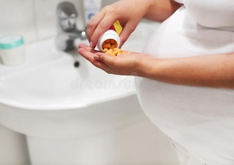 Zwangere vrouw in badruimte die pillen nemen stock afbeeldingen