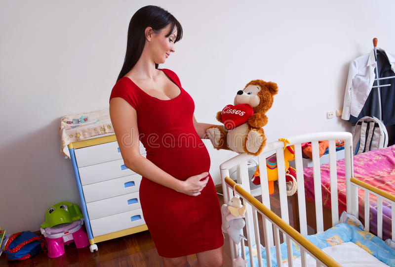 Zwangere vrouw dichtbij babywieg stock foto