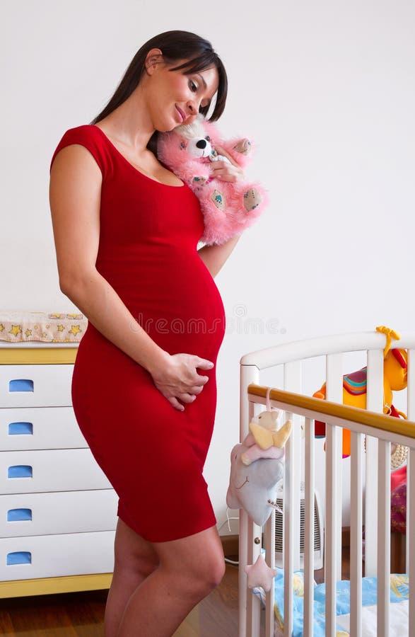 Zwangere vrouw dichtbij babywieg royalty-vrije stock afbeeldingen
