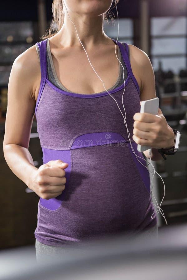 Zwangere vrouw die aan muziek luistert stock afbeelding