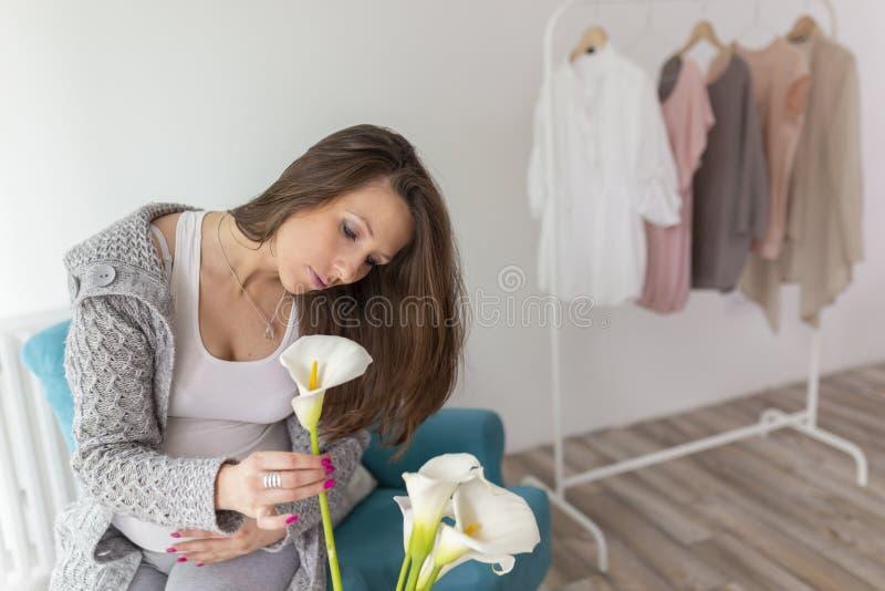 Zwangere vrouw die bloemen schikt royalty-vrije stock foto's