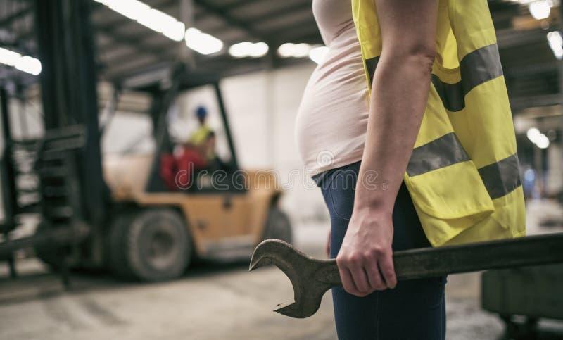Zwangere vrouw die in bouwfabriek werken royalty-vrije stock foto's