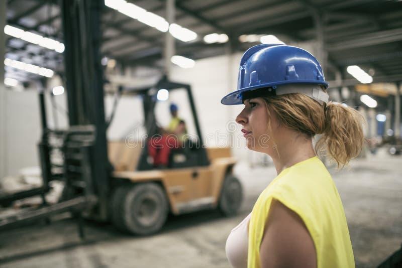 Zwangere vrouw die in bouwfabriek werken stock foto