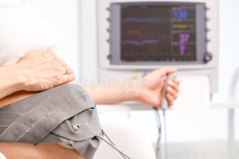 Zwangere vrouw die cardiotocography CTG uitvoeren die foetale hartslag controleren stock afbeelding