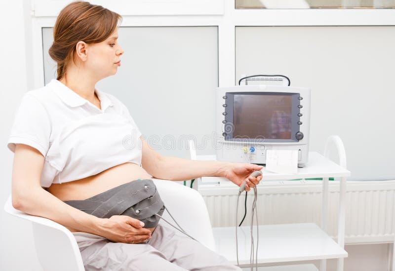 Zwangere vrouw die cardiotocography CTG uitvoeren die foetale hartslag controleren royalty-vrije stock fotografie
