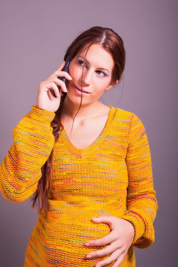 zwangere vrouw die celtelefoon met behulp van stock foto