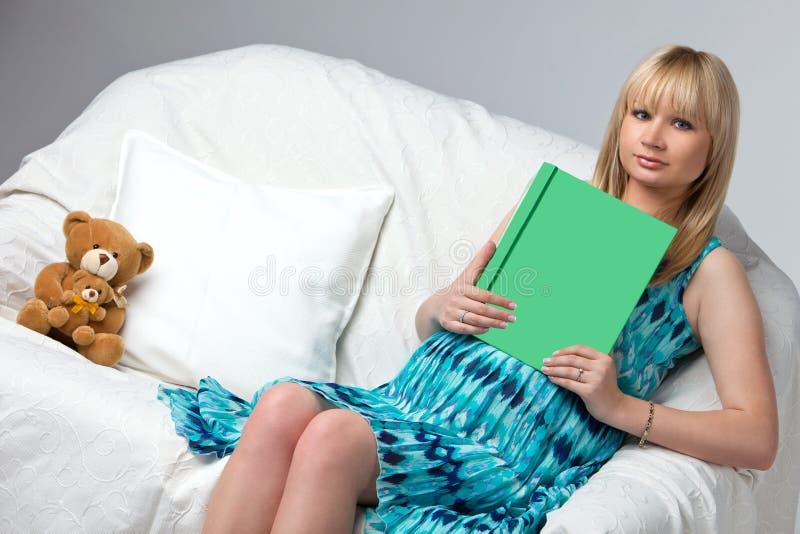 Zwangere vrouw die een boek op bank lezen Een boek met vrije tekstruimte royalty-vrije stock fotografie