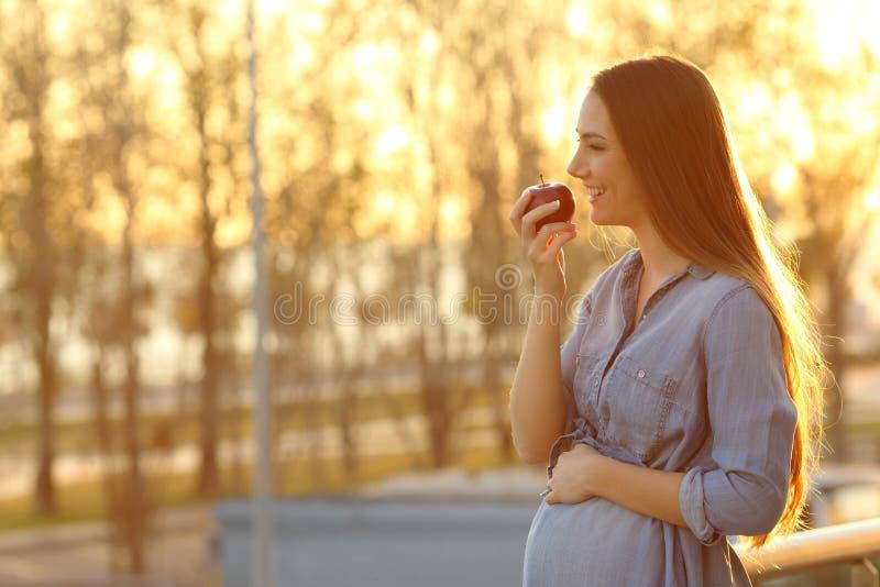 Zwangere vrouw die een gezonde appel eten royalty-vrije stock afbeelding