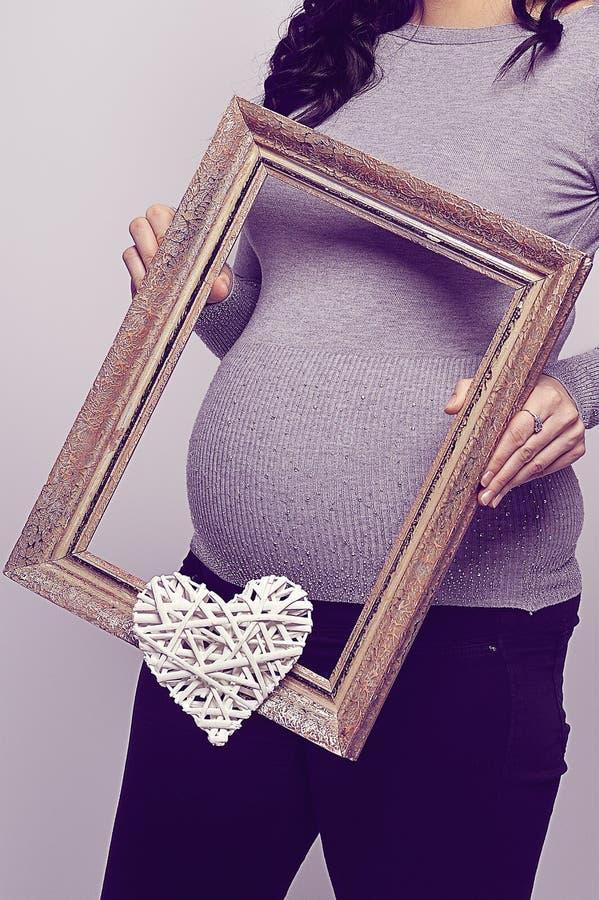 Zwangere vrouw die een hart van kaderwiths houden royalty-vrije stock fotografie
