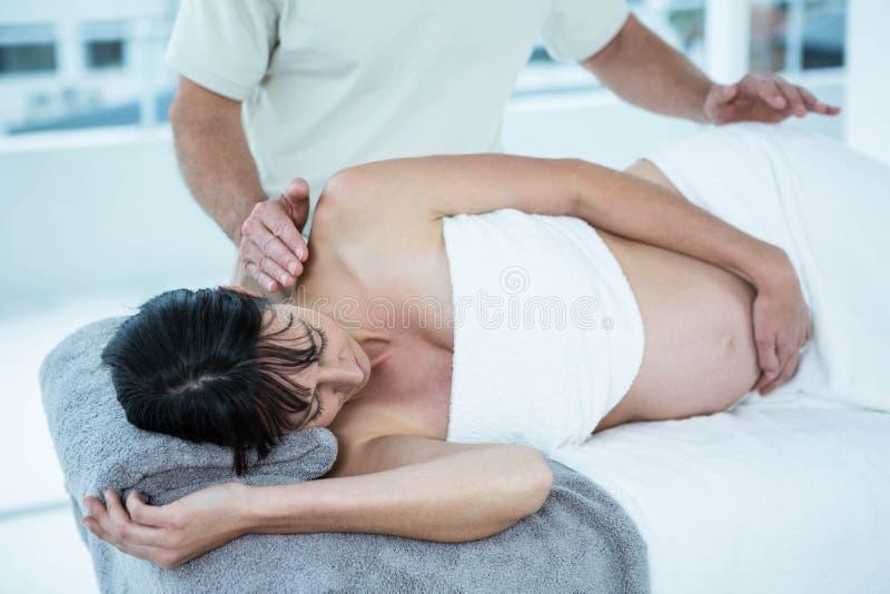 Zwangere vrouw die een massage van masseur ontvangen royalty-vrije stock foto's