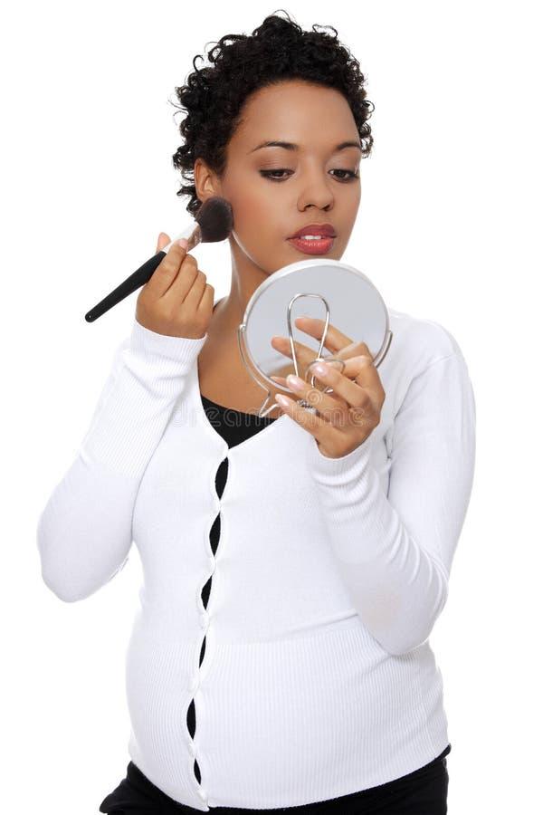 Zwangere vrouw die een merk omhoog doet. stock foto's
