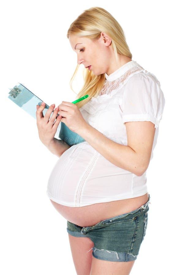 Zwangere vrouw die een nota schrijft stock foto's