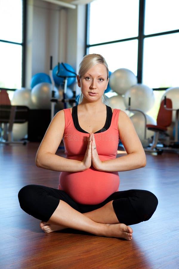 Zwangere vrouw die en buik ontspant houdt. stock afbeelding