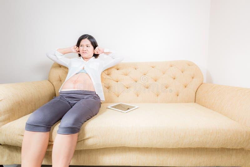Zwangere vrouw die ernstig zittend op laag kijken royalty-vrije stock foto