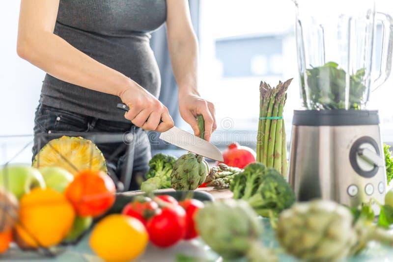 Zwangere vrouw die gezond voedsel koken stock afbeeldingen