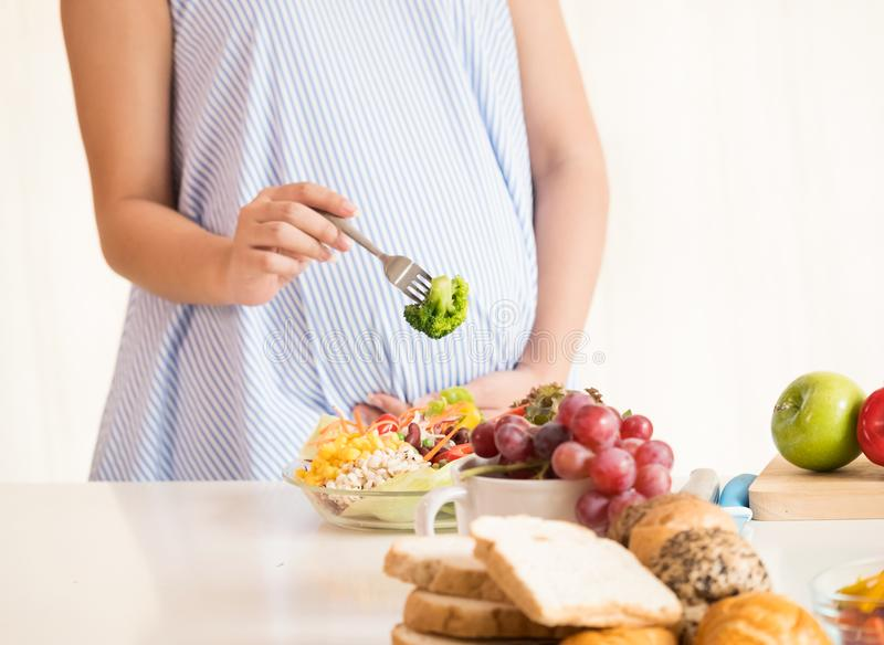Zwangere vrouw die gezonde verse salade, gezonde voedingsduri eten stock fotografie