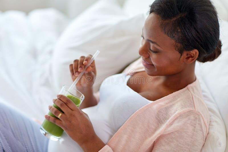 Zwangere vrouw die groentesap in bed drinkt royalty-vrije stock foto's