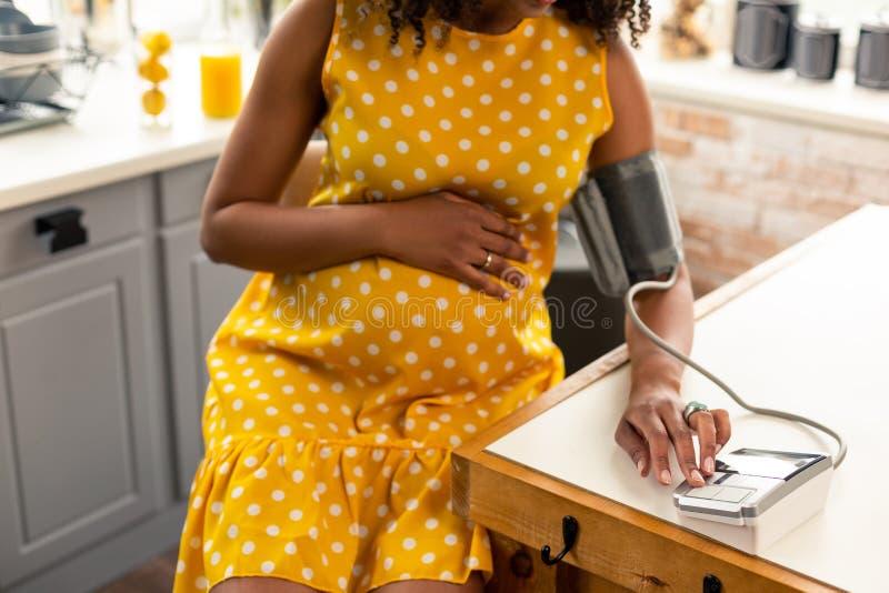 Zwangere vrouw die haar bloeddruk in keuken meten stock foto's